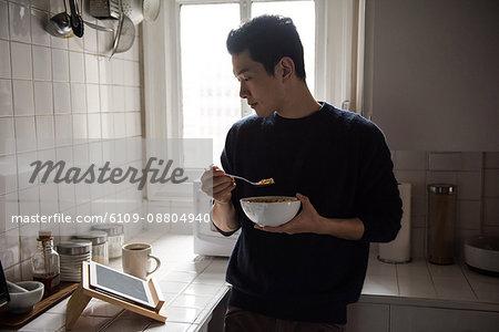 Man using digital tablet while having breakfast at home