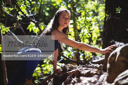 Woman trekking on mountain in forest
