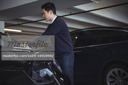 Man using laptop while charging electric car in garage