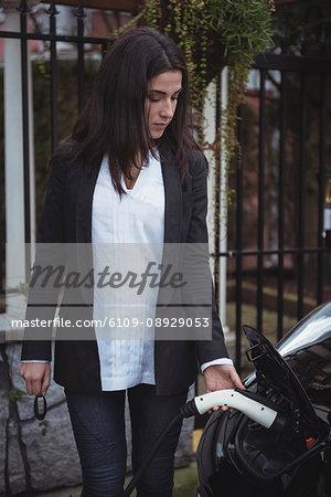 Beautiful woman charging electric car at vehicle charging station