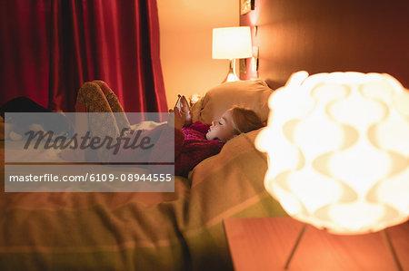 Girl sitting using digital tablet in bedroom at home