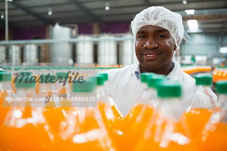 Portrait of happy male worker standing by orange juice bottles in factory