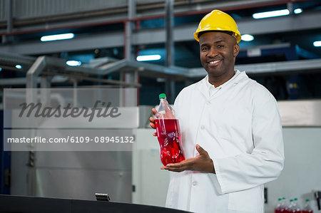 Portrait of male worker showing juice bottle in factory