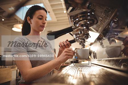 Young female barista making espresso in coffee shop