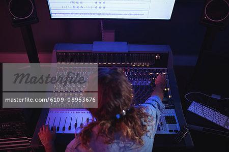 Male audio engineer using sound mixer in recording studio