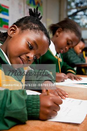 A young girl writing at a desk, Meyerton Primary School, Meyerton, Gauteng