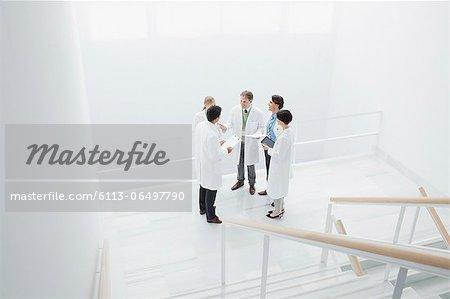 Doctors meeting on landing of stairs