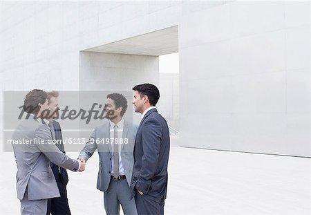 Smiling businessmen shaking hands outside cultural center