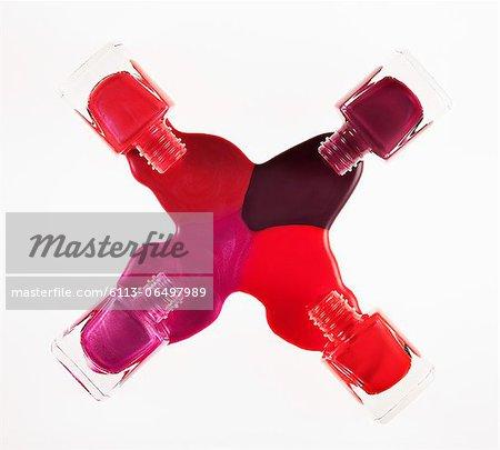 Multicolor fingernail polish spilling from bottles