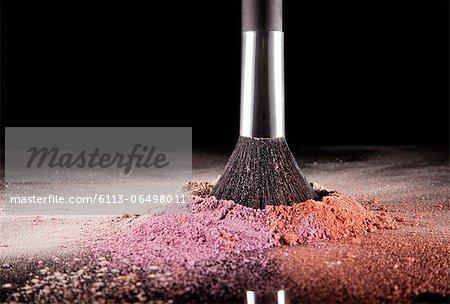 Makeup brush dipping into multicolor blush splatter