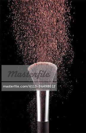 Blush powder blowing from makeup brush