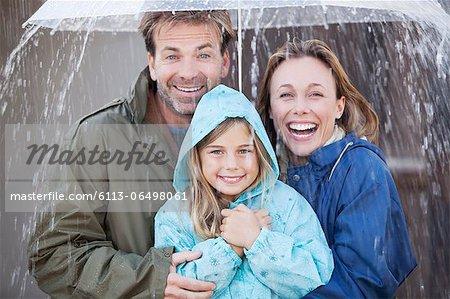 Portrait of enthusiastic family under umbrella in downpour