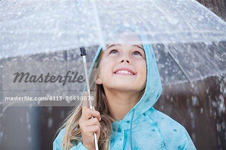 Close up of smiling girl under umbrella in downpour