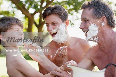 Playful multi-generation men applying shaving cream to faces