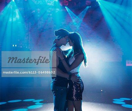 Couple dancing and kissing under spotlights on empty dance floor of nightclub