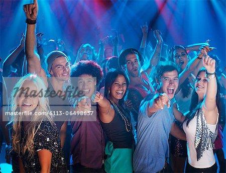 Portrait of enthusiastic crowd on dance floor of nightclub