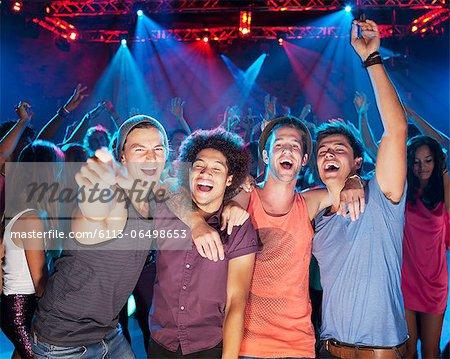 Enthusiastic friends cheering on dance floor of nightclub
