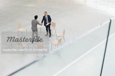 Circle of chairs around businessmen shaking hands