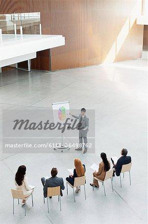 Businessman at flipchart leading meeting in modern lobby