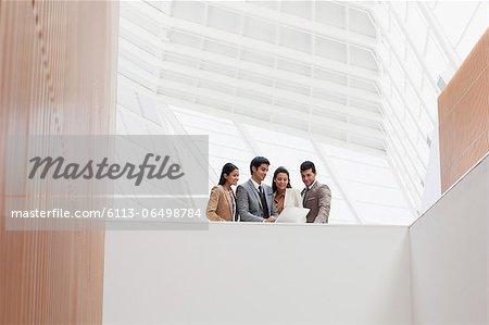 Business people reviewing paperwork in modern building