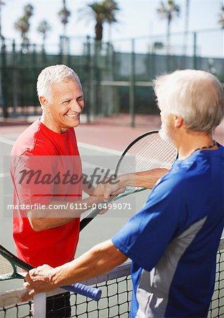 Older men shaking hands on tennis court