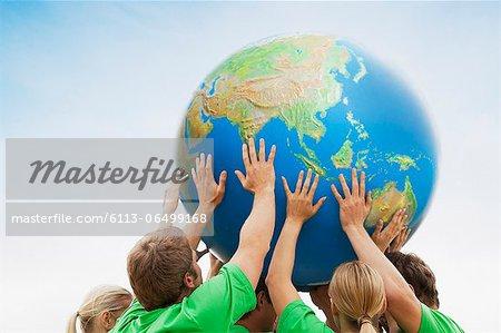 Team in green t-shirts lifting globe overhead