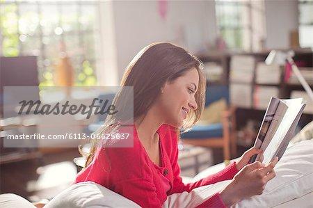 Woman reading magazine on sofa