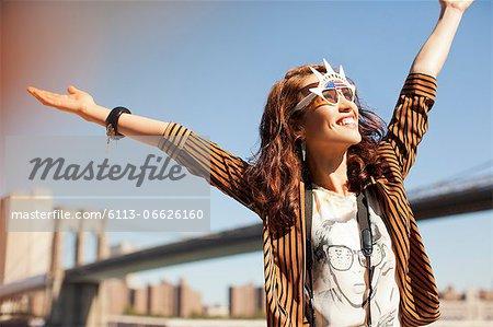 Woman in novelty sunglasses standing by urban bridge