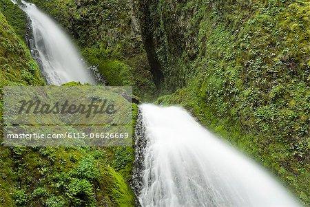 Waterfall rushing over green rocky hillside