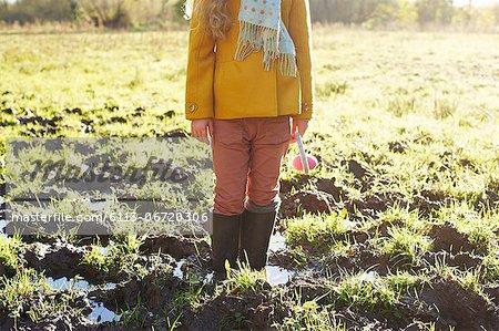 Girl standing in muddy field