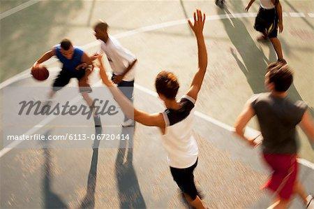 Men playing basketball on court