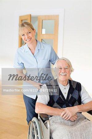 Caregiver pushing older man in wheelchair