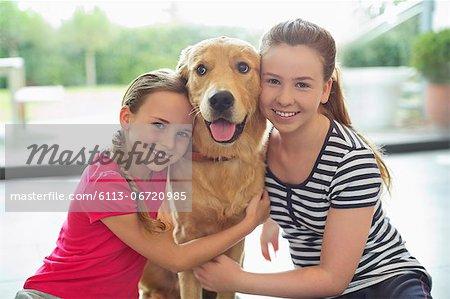 Smiling girls hugging dog indoors