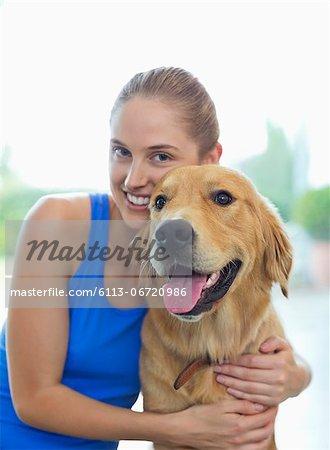 Smiling woman hugging dog indoors