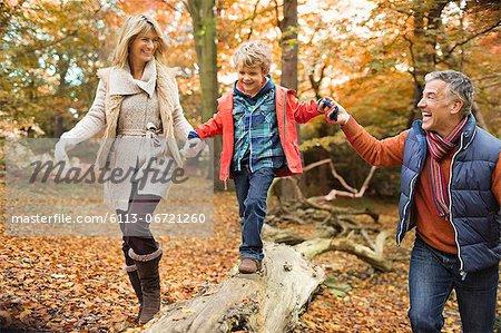 Family walking on log in park