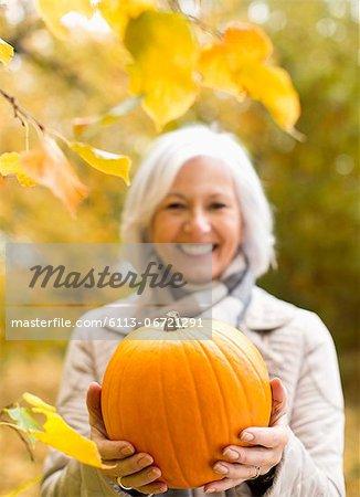 Older woman holding pumpkin in park