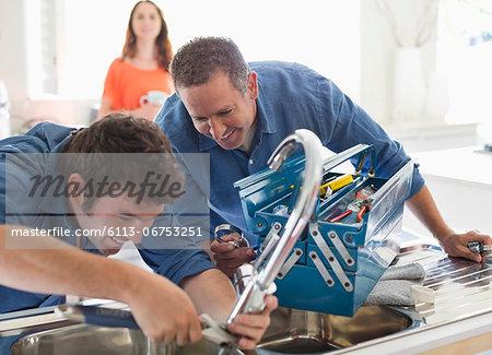 Plumbers working on kitchen sink