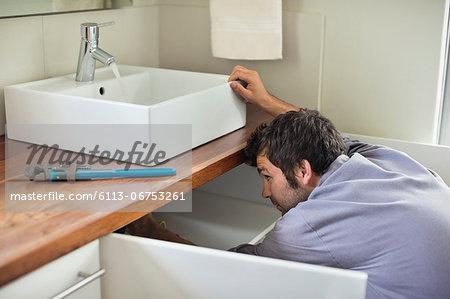 Plumber working under kitchen sink