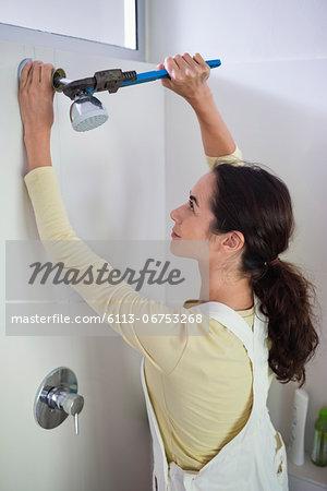 Woman working on shower head in bathroom