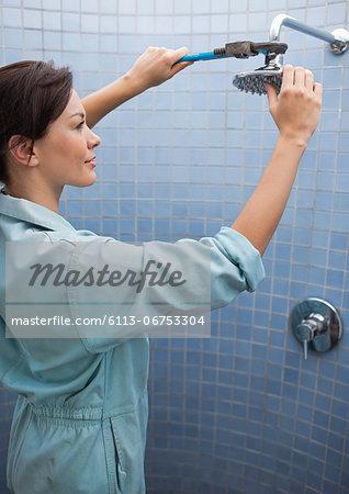 Female plumber working on shower head in bathroom