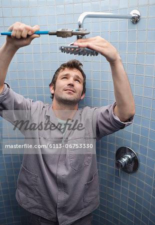 Plumber working on shower head in bathroom