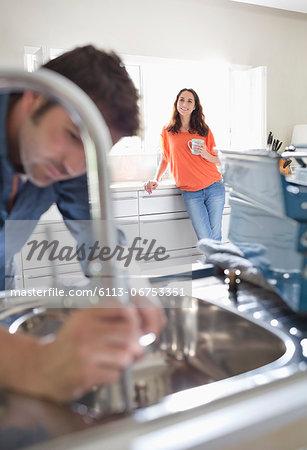 Woman watching plumber work on kitchen sink