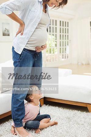 Girl holding pregnant mother's legs
