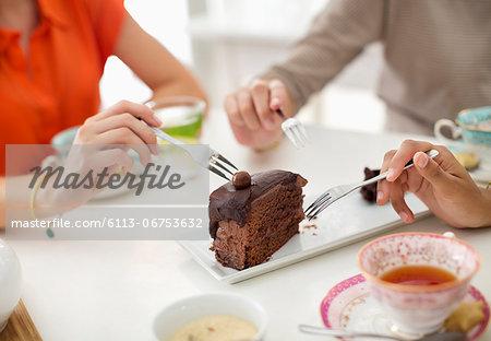 Women sharing slice of cake