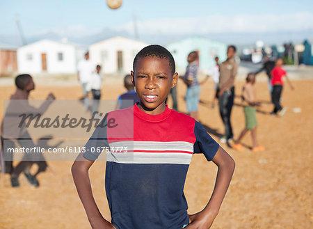 Boy standing in dirt field