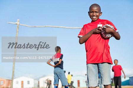 Boy holding soccer ball in dirt field