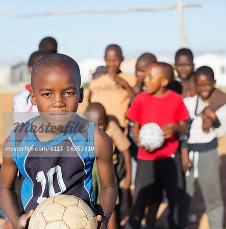 Boys holding soccer balls in dirt field