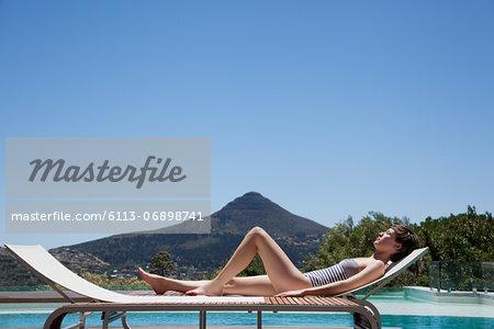 Woman sunbathing lounge chair poolside