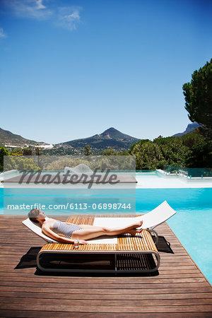 Woman sunbathing at poolside