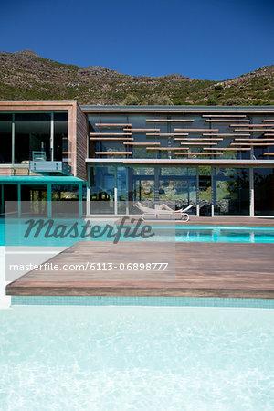 Woman sunbathing poolside of modern house